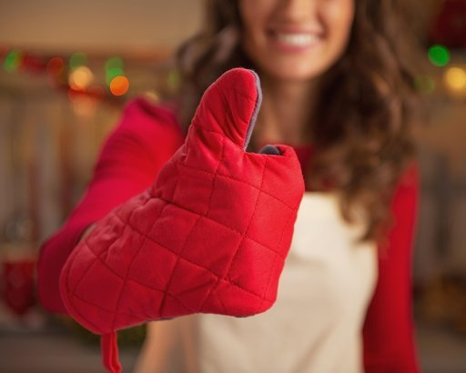 closeup on young housewife in kitchen gloves showing thumbs up in christmas decorated kitchen
