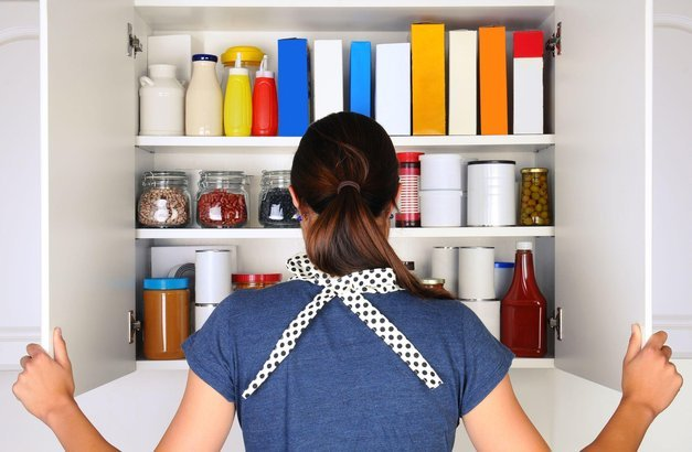 woman seen from behind opening the doors to a fully stocked pantry