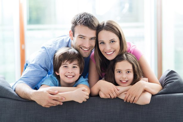 family smiling together on top of a sofa