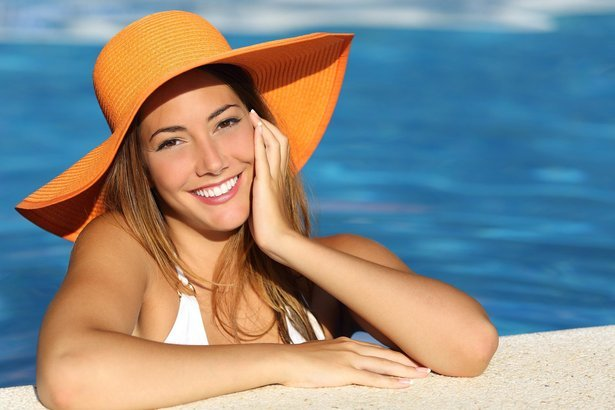 woman sitting on the slide of the pool with an orange hat