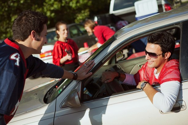 football fan arrives to tailgate party in car