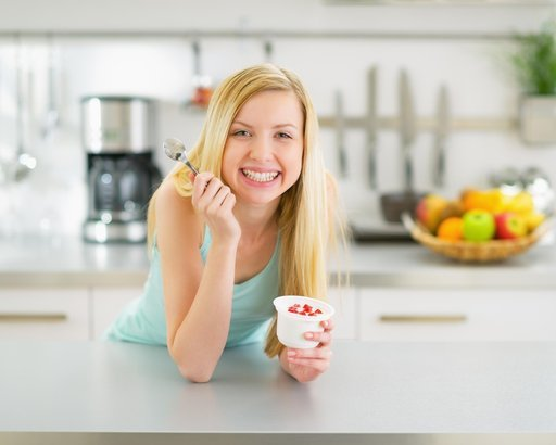 woman eating yogurt on kitchen countertop