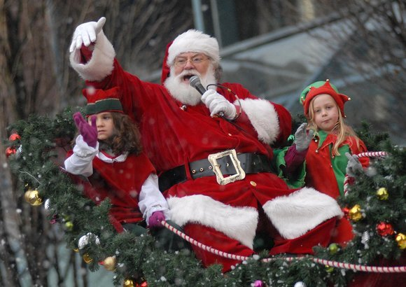 santa talking to the crowd in a parade