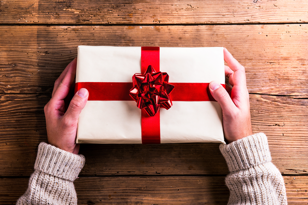 Closeup of man's hands holding Christmas gift