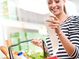smiling young woman holding a long grocery receipt at supermarket