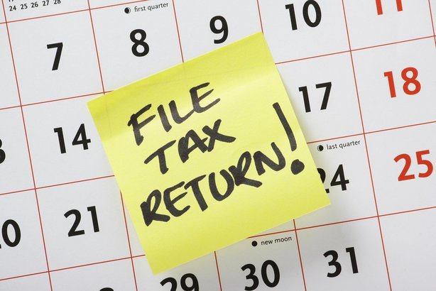 Hand written reminder to 'File Tax Return' on a yellow post it note stuck to a calendar