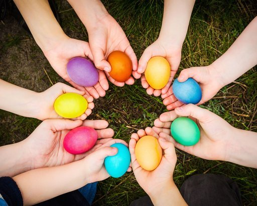 children hands holding colorful easter eggs