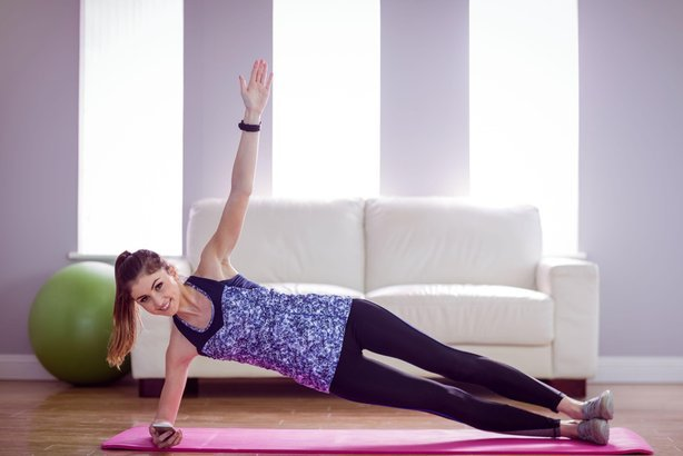 fit woman doing side plank at home in the living room