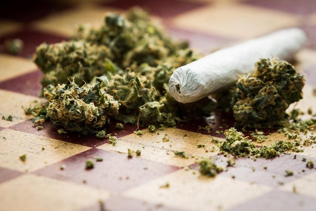 closeup of marijuana joint and buds on a checkerboard table