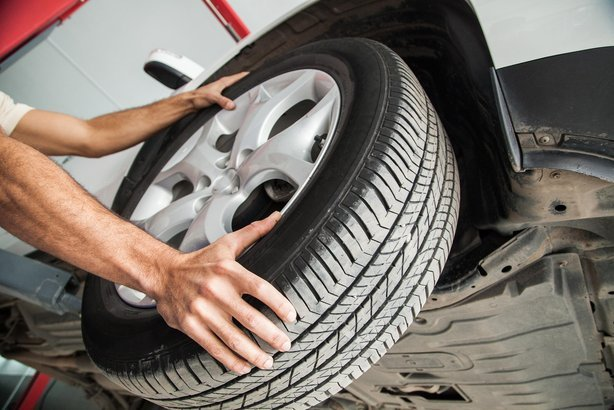 car mechanic's hands installing tire