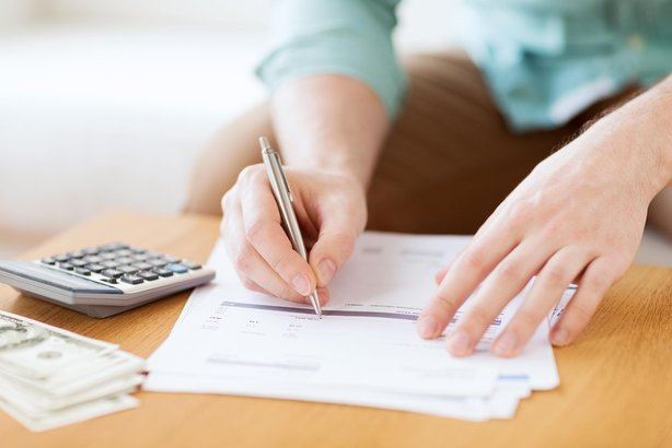 man's hands with calculator counting money and making notes at home