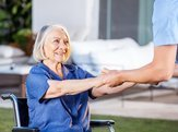 male nurse helping senior woman to get up from wheelchair at nursing home