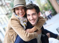 happy couple with woman piggy backing on guy