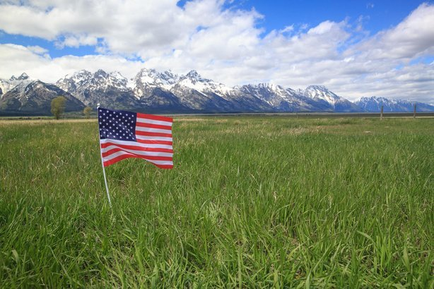 American Flag on green meadow in the Rocky Mountains