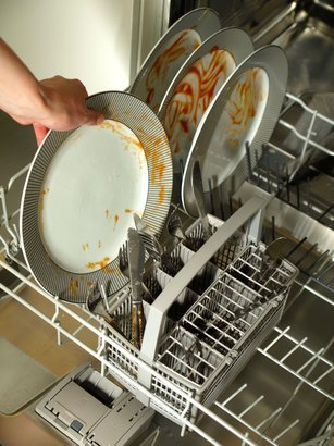 putting dirty plates in the dishwasher after dinner