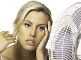 woman keeping cool with fan