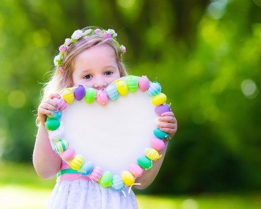 little girl holding easter decoration outside