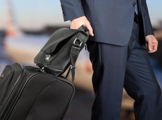 businessman in a modern stylish suit with luggage in the airport