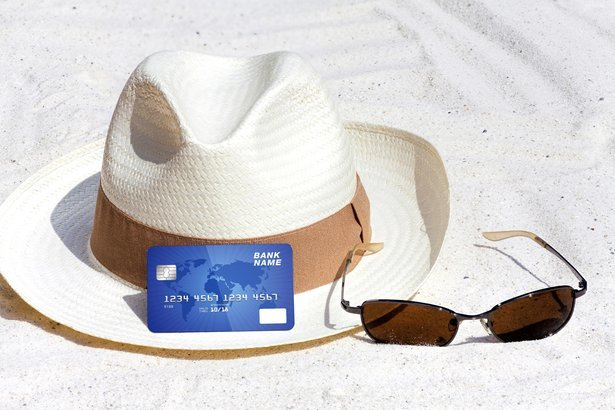 hat and sunglasses in sand with credit card