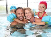 family having fun in public indoor swimming pool