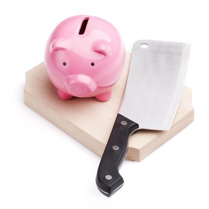 piggy bank and kitchen knife on cutting board