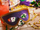 Mardi Gras party mask with festive decorations and trinkets