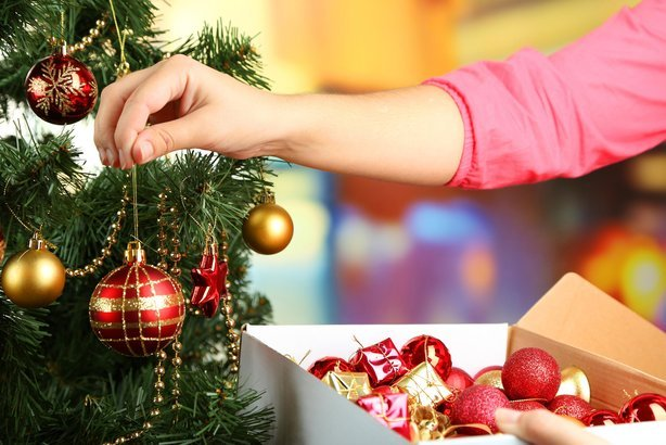 woman decorating tree with ornaments