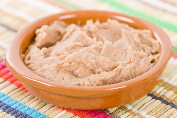 bowl of Mexican refried beans on a colorful background
