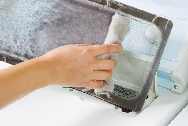 female hand taking the lint out from dirty air filter of the dyer machine