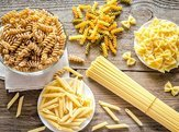 various types of pasta in dishes on table