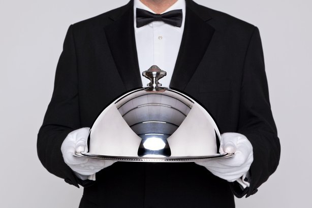 waiter serving a meal under a silver cloche