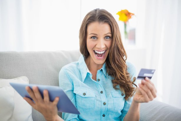excited woman with credit card and tablet on couch