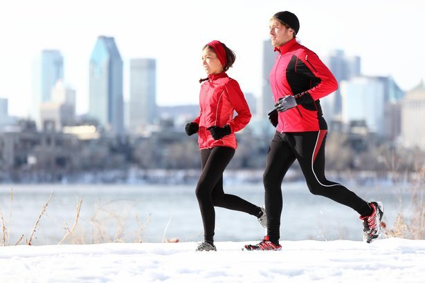 couple running in winter snow with city skyline in the background