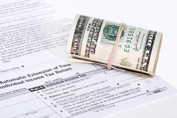 roll of USD cash near an IRS tax form