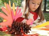 child making pine cone turkey outside
