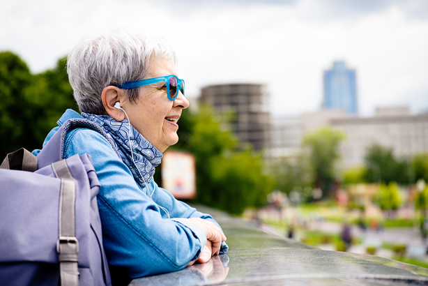 Senior woman looking out over a downtown city