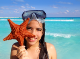 Young girl in Mexico holding a starfish