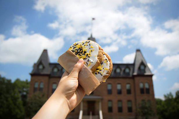 Hand holding a cookie up to the sky with college in background