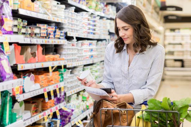 Woman looking at yogurt in a grocery store