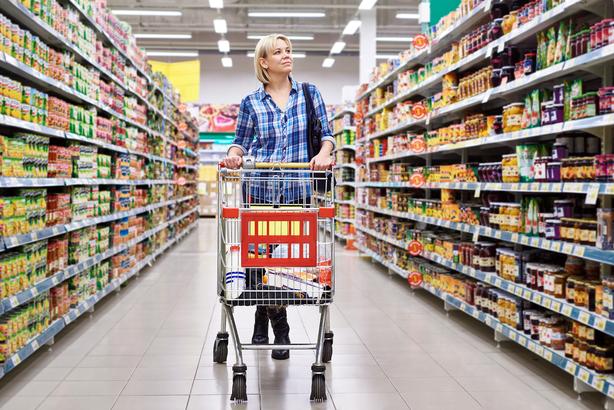 Woman walking down a grocery store aisle