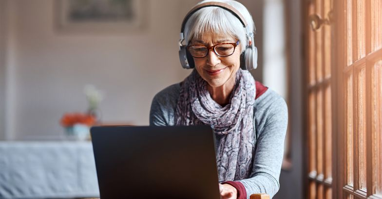 Senior woman on her laptop wearing headphones