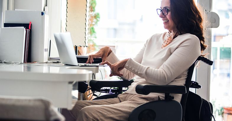 Woman in a wheelchair smiling while on her computer