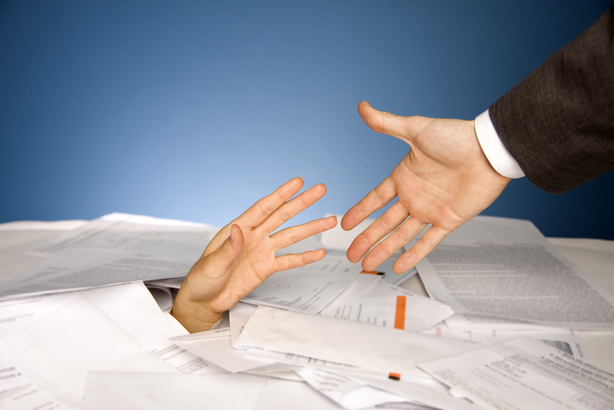 Hand buried under bills reaching for help