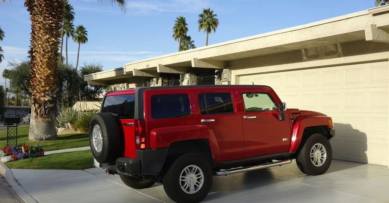 Red Hummer H3 SUV parked on residential diveway