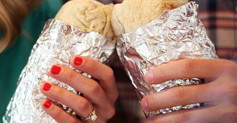 Couple holding Chipotle burritos