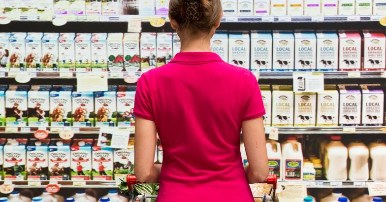 Woman in front of milk at grocery store