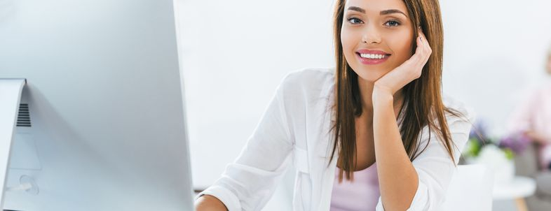 Smiling attractive girl using computer at home
