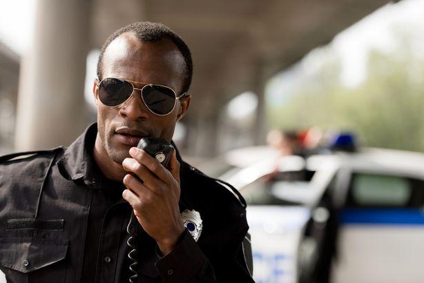 Police officer speaking into walkie talkie
