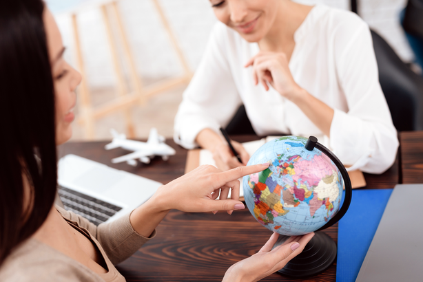 Travel agent showing a globe to a client