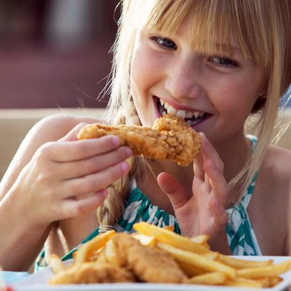 Girl eating chicken strips at Eats Kitchen